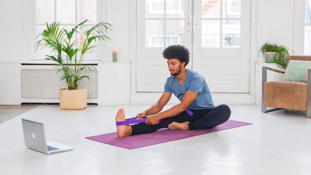 Man using a yoga strap in a yoga forward fold