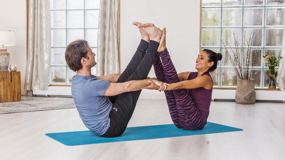 Partner boat pose yoga practice